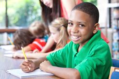 school boy smiling at desk